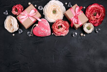 Festive Romantic Border With Peony Flowers, Gift And Hearts On Black Background. Top Down Composition With Copy Space.