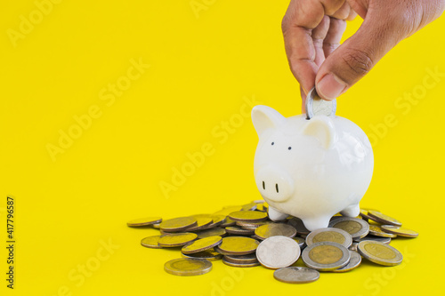 Fotografija White piggy with coins thai baht and hand putting money on yellow background, save or investment concept