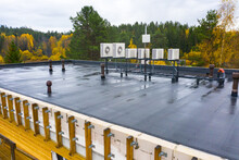 Lots Of Rooftop Air Conditioning Units. Coniferous Forest In Background. Concept - Installation Of A Ventilation System. Installation Of Air Conditioning Systems. Conditioners For Industrial Premises