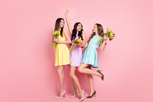 Photo Of Three Cute Carefree Young Ladies Wear Colorful Dresses Holding Flowers Bouquets Isolated Pink Color Background
