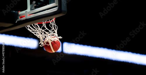 Obraz na płótnie The orange basketball ball flies through the basket