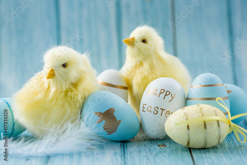 Blue, yellow, white Easter eggs in the nest and yellow chicks on a blue wooden background Fototapete