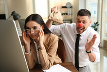 Man Popping Paper Bag Behind His Colleague In Office. Funny Joke