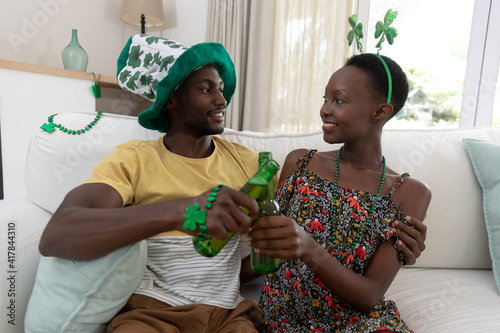 Smiling african american couple in st patrick's day costumes embarcing and raising bottles of beer