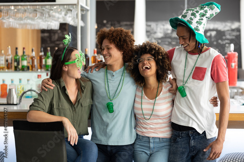Diverse group of friends celebrating st patrick's day embracing and laughing at a bar
