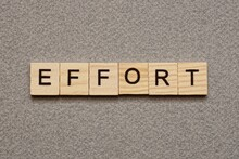 Text The Word Effort From Brown Wooden Small Letters With Black Font On An Gray Table
