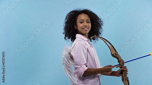 Fotografering happy african american girl with wings holding crossbow isolated on blue