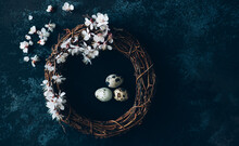 Easter Background With Easter Eggs And Spring Flowers. Eggs In Nest On Dark Vintage Wooden Background.