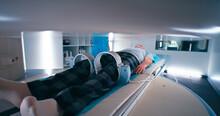 Multiethnic Doctors Releasing Aged Patient From MRI Machine