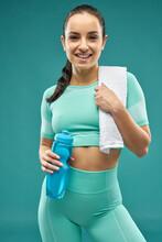 Joyful Young Woman In Sportswear Holding Bottle Of Water