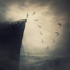 Surreal scene, determined man jumping off a cliff, fighting his fears, being confident the wings will unfold in flight. Free fall before flying. Self confidence, courage concept, way to success