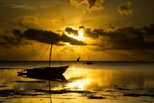 A Sunrise At Low Tide With Fishermen And Traditional Ngalawa Boats In Foreground, Near Jambiani, Zanzibar, Tanzania.