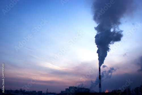 Fotografia large chimney with black smoke against the background of the sunset sky on