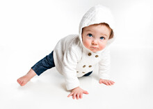 Portrait Of Cute Active Baby Crawling In The Studio, Wearing White Hoodie, Wintertime Fashion For Children