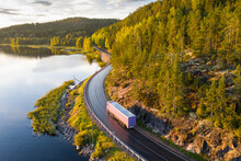 Aerial View Of Semi Truck With Cargo Trailer On Road Curve At Lake Shore With Green Pine Forest. Transportation Background. Beautiful Nature Landscape At Sunset In Republic Of Karelia, Russia