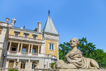 Sphinx With Female Head Against Building Of Massandra Palace. Complex Was Founded In 1881 By Prince Vorotsov. Now It's Popular Tourist Place For Walking. Shot Near Yalta, Crimea