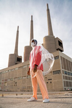 Man Wearing Raincoat And Protective Face Mask Looking Away While Standing Against Building