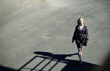 Young Woman Walking On Road During Sunny Day