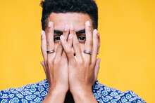 Man Covering Face With Hands Against Yellow Background