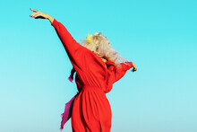 Carefree Woman With Arms Outstretched Against Blue Sky On Sunny Day