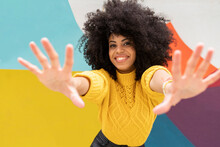 Smiling Woman Stretching Hands While Standing Against Colorful Wall