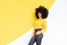 Curly Hair Woman With Hands In Pockets Leaning On Wall