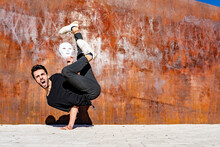 Young Man With White Mask Shouting While Doing Handstand Against Brown Wall