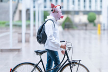Young Man With Bicycle Wearing Pig Mask Listening Music Through Headphones