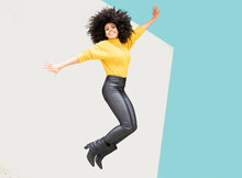 Carefree Woman With Arms Outstretched Jumping Against Yellow And Blue Wall