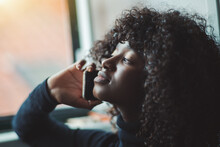 Close-up Portrait With A Shallow Depth Of Field And A Selective Focus Of A Ravishing Young Black Female With Curly Afro Hair, Talking On The Phone While Sitting Next To The Window And Looking Outside