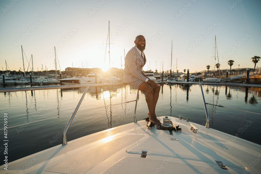 Fototapeta A cheerful elegant mature bald bearded black man in a summer suit consisting of striped shorts and blazer is sitting on the railings of his luxurious yacht, laughing and enjoying the dramatic sunset