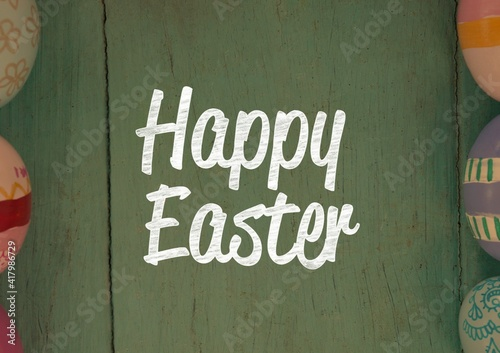 Happy easter text with easter eggs on green wooden background