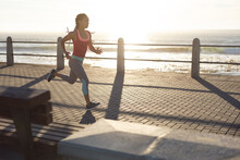 African American Woman Exercising On A Promenade By The Sea Jogging