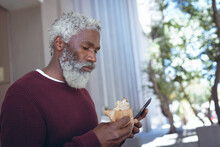 African American Senior Man In Street Eating Sandwich And Using Smartphone