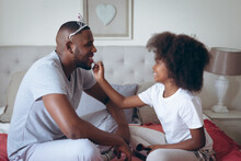 African American Man Wearing Tiara Having Makeup Put On By His Daughter