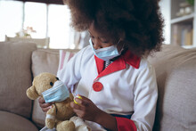 African American Girl Playing Doctor And Patient With Her Teddy Bear