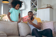 African American Girl Standing In Living Room Giving Her Father A Present