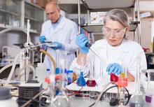 Professional Female Chemist Working In Laboratory, Mixing Chemical Agents During Experiment..