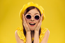 Happy Woman In A Yellow Hat And Fashionable Glasses Holds Her Hands Near Her Face On A Yellow Background Cropped View Of Emotions Fun
