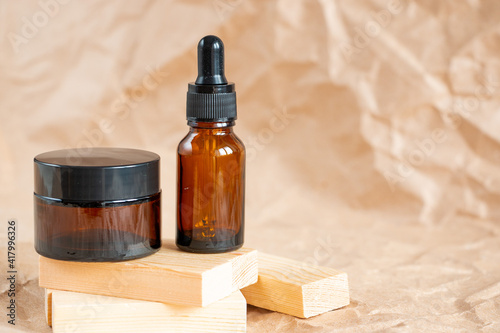 Fotografiet Cometic bottles made of amber glass on crumpled craft paper