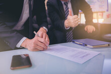 Businessman Puts Signature On Contract At Business Meeting And Passing Money After Negotiations With Business Partners. Selected Focus