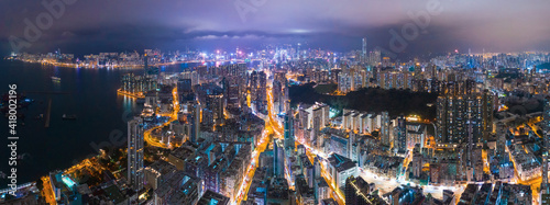 Epic aerial night view of downtown district in Kowloon, Hong Kong. Graded to Cyperpunk color