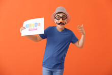 Little Boy In Funny Disguise And With Poster On Color Background. April Fools Day Celebration