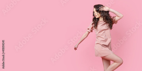 Obraz Beautiful fashionable girl with long curly hair in a pink dress in the studio on a pink background. Advertising, hair products, beauty salon, cosmetics, clothing. Fashion, boutique. Pink. - fototapety do salonu