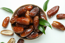 Bowl Of Dried Dates With Leaves On White Background