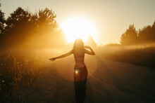 Silhouette Of A Woman Dancing By A Road At Sunset, Russia