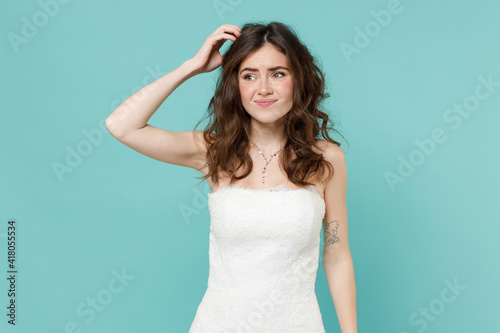 Obraz Puzzled confused pensive worried bride young woman 20s in beautiful white wedding dress put hand on head isolated on blue turquoise wall background studio portrait. Ceremony celebration party concept. - fototapety do salonu