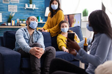 African Woman Showing Funny Clip On Smartphone Hanging Out In Home Living Room Wearing Face Mask Preventing Coronavirus During Global Pandemic Keeping Social Distancing.