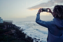 Traveling By Portugal. Young Woman Taking Photo Of Wonderful Sunset On Rock Ocean Shore.