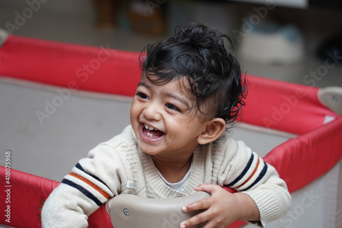 Fototapeta A closeup photo of an adorable indian toddler baby boy smiling with dimple in ch